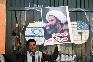 Houthi Holds Gun, al-Nimr Sign in front of US & Israeli Flags (Photo Credit- EPA)