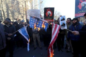 Iranian protesters holding pictures of Shi'ite cleric Sheikh Nimr al-Nimr burn a U.S. flag (R) and an Israeli flag during a demonstration at the KSA Embassy in Tehran (Photo Credit: Reuters)