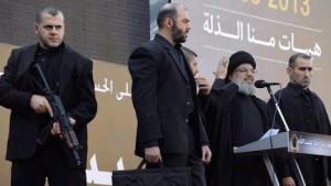 Nasrallah on stage with armed guard and suitcase with ballistic protection against assassination attempts, which is bulletproof and bombproof (Photo Credit- Ynet)